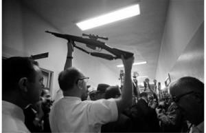 Carl Day (1914-2008) mostra ai giornalisti nella centrale di Dallas il fucile ritrovato al sesto piano del deposito libri